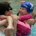 Dolfijnouder laat kinderen spelen. Foto: Tommy Wong, Flickr