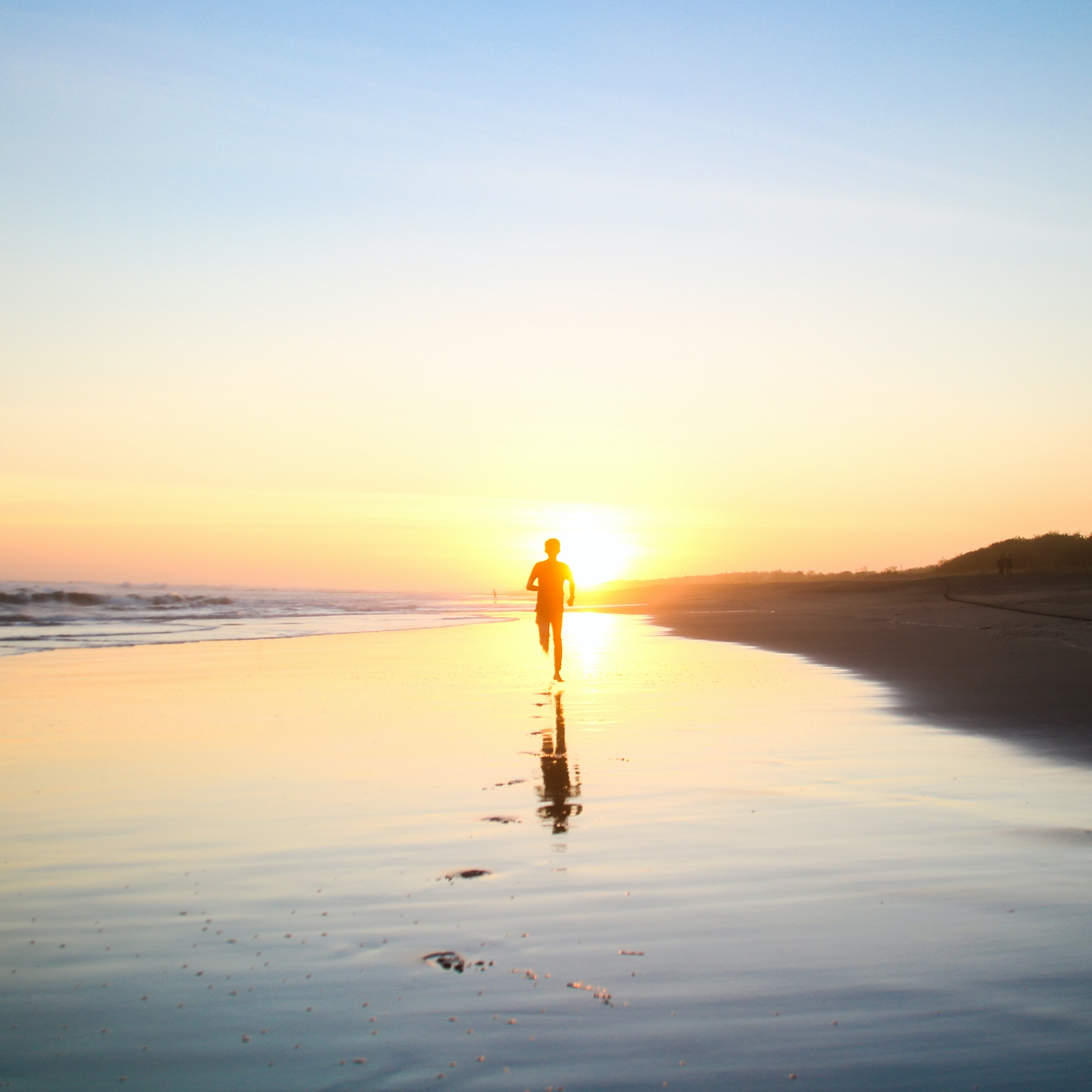 silhouette-of-boy-running-in-body-of-water-during-sunset-694587