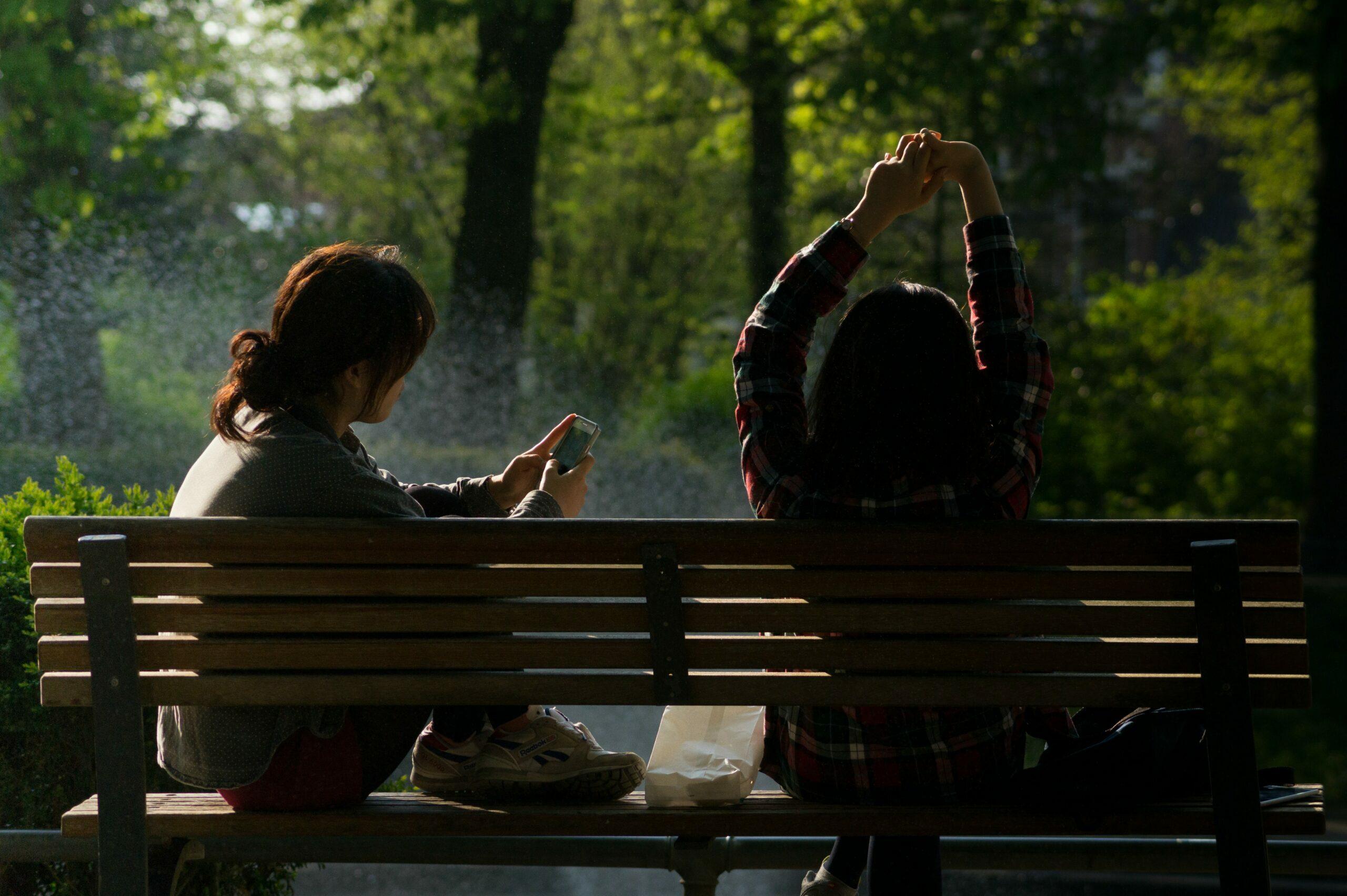 tijd miljonairs; twee vrouwen luieren op een bankje buiten